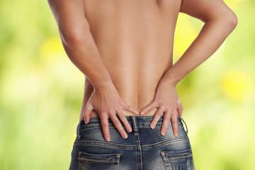 junge Frau in Jeans hat Schmerzen im unteren Rücken