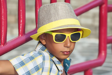 Beautiful funny child with sunglasses and hat on vacation