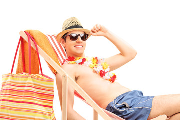 Shirtless young man sitting on a sun lounger