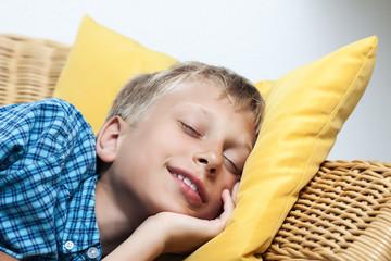 Beautiful little boy sleeping peacefully on wicker sofa