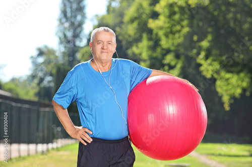 Mature man holding a fitness ball in park