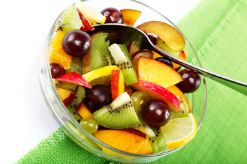Salad of fresh fruits and berries on a green cloth.