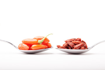 piles of fresh and dry goji berry in spoons on white background