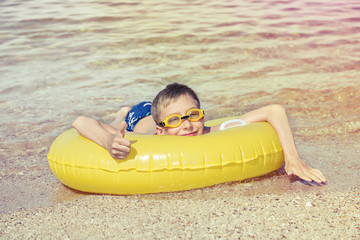 Funny chilld with swimmer goggles lying on float on beach