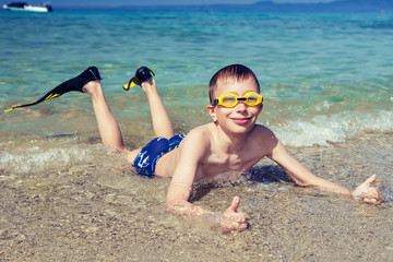 Happy child diver lying on beach smiling showing thumbs up