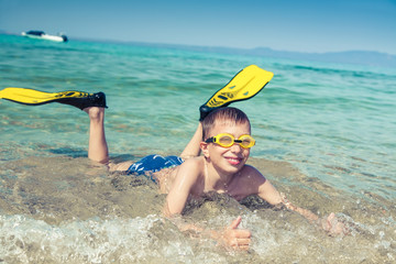 Happy child diver in swimware lying on beach showing thumbs up