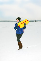 Woman running with package in the winter landscape