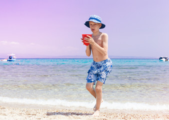 Funny child with panama running on beach holding toy bucket