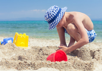 Funny little child with panama playing on beach building castle