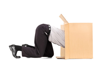 Businessman squeezing himself into a box