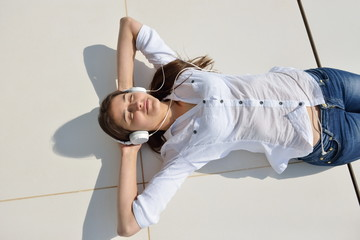 girl listening to the music on white headphones