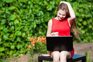 Девушка за ноутбуком на природе
