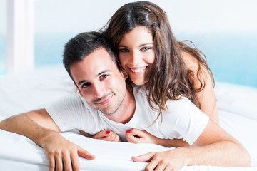 Portrait of cute couple on bed.