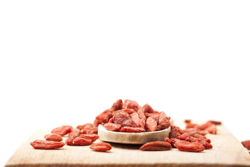 a pile of dried goji berry in wooden spoon on white background
