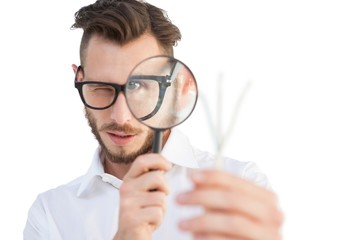 Nerdy businessman looking through magnifying glass