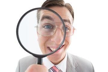 Excited businessman looking through magnifying glass
