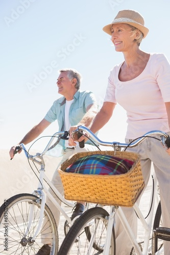 Happy senior couple going for a bike ride - 69302672