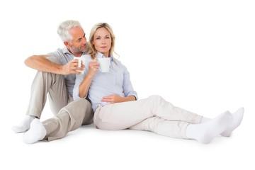 Happy couple sitting holding mugs