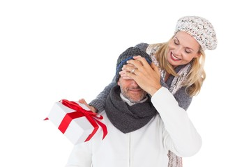 Happy woman holding gift while covering husbands eyes