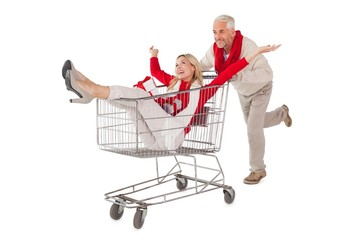 Festive couple messing about in shopping trolley