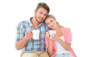 Attractive young couple sitting holding mugs