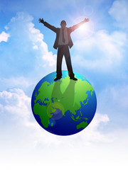 Silhouette of a man figure standing on globe with open arms