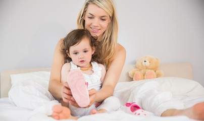 Mother helping daughter in wearing her shoe on bed