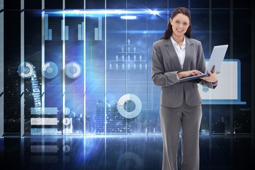 Composite image of businesswoman smiling with a laptop