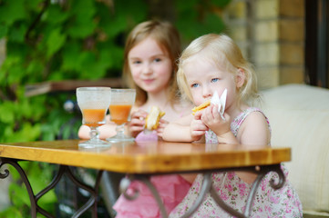 Two sisters drinking juice and eating pastries