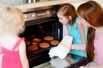 Mother and daughters baking cookies