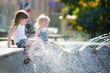 Two cute little girls playing with a city fountain