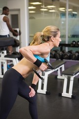 Side view of fit woman exercising with dumbbell in gym
