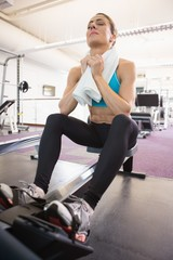 Tired young woman sitting in gym