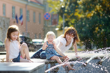 Young woman and two kids by a city fountain