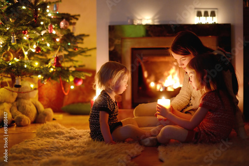 Happy family by a fireplace on Christmas - 69303447