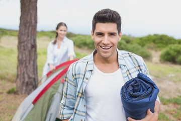 Couple with tent walking on countryside landscape