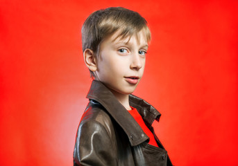 Beautiful stylish boy wearing leather coat on red background