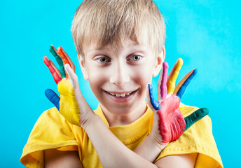 Beautiful cheerful boy in yellow t-shirt showing painted hands