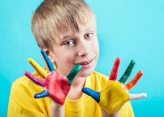 Beautiful cheerful boy in t-shirt showing painted hands