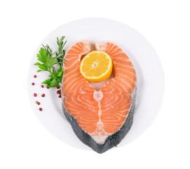 Raw salmon steak with parsley and lemon slice.
