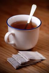 tazza di tè con bustine intorno