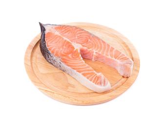 Fresh salmon steak on wooden platter.
