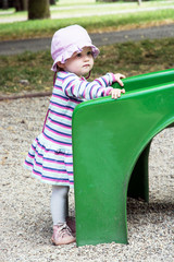 Little baby girl and playground slide