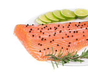 Uncooked salmon fillet with lime and herbs.