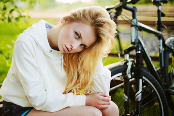 Beautiful girl sitting against bike outdoor in the park