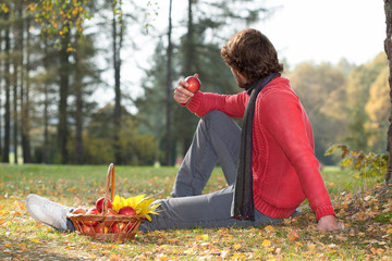 Man eating apple in the park