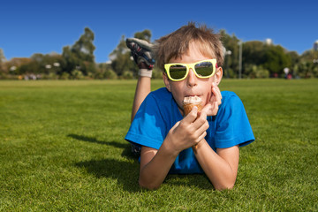 Funny boy with sunglasses lying on grass eating ice-cream