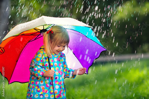 Funny cute toddler girl wearing raincoat with colorful umbrella - 69307097