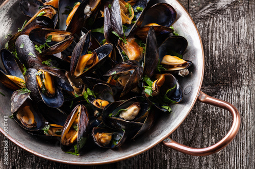 Leinwandbild Motiv Boiled mussels in copper cooking dish on dark wooden background