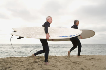 Male surfers in wetsuits on beach, side view